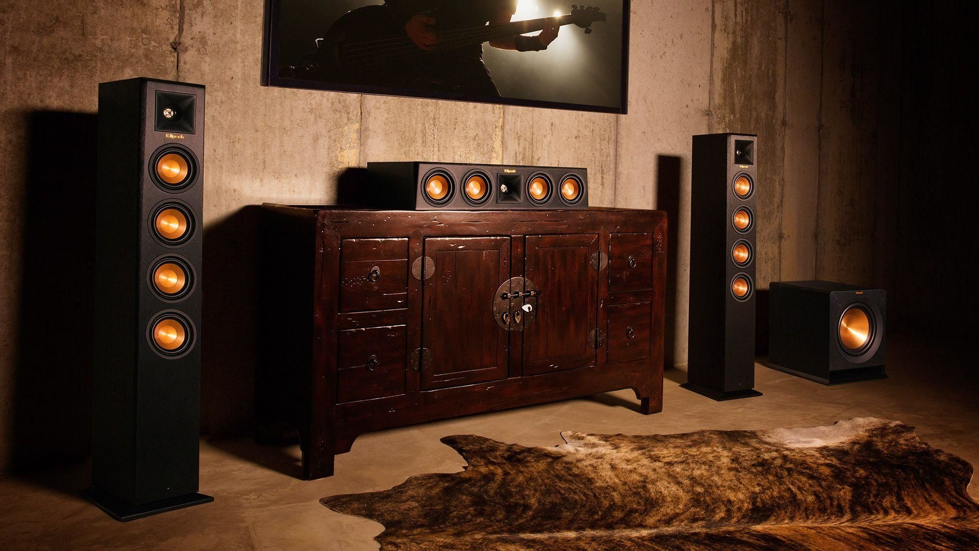 Klipsch wireless speakers flanking a tv and wood cabinet