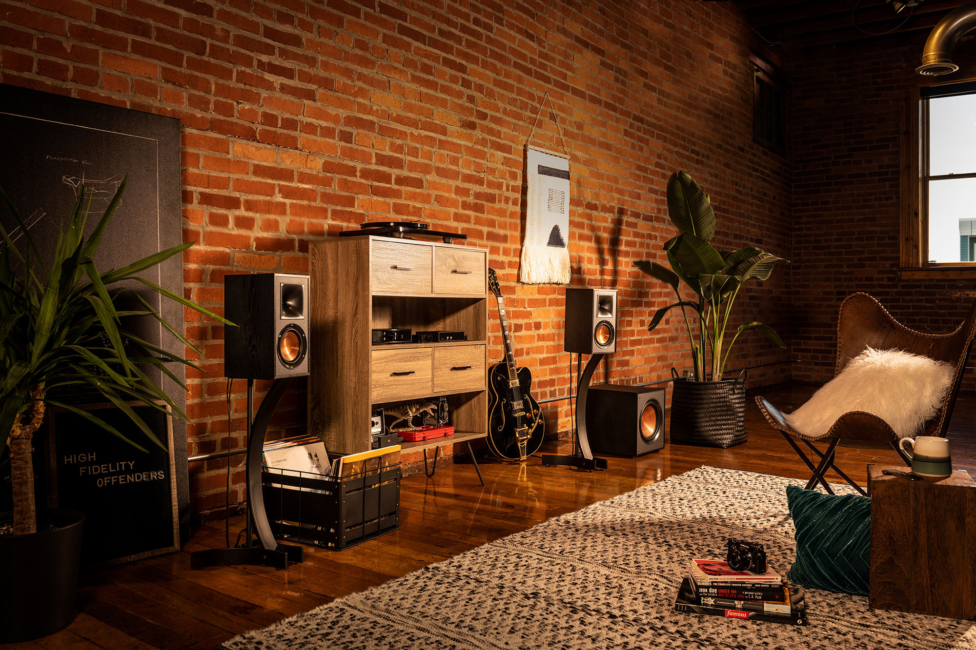 Klipsch Reference bookshelf speakers and subwoofer next to a guitar and wood cabinet
