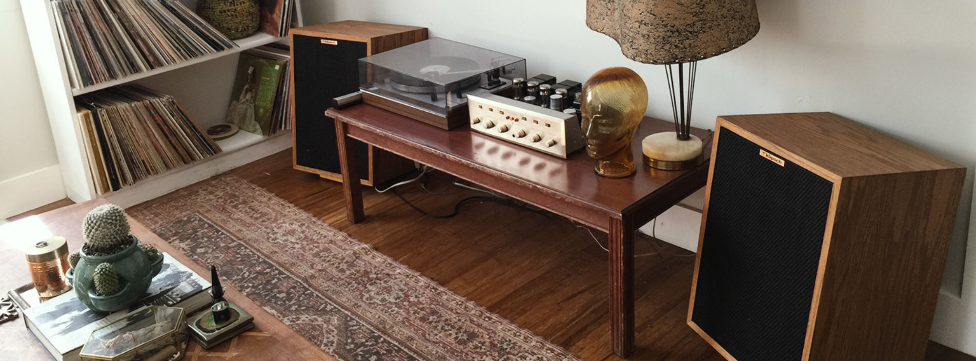 Two Heresy speakers flanking a wood table with a turntable and amplifier
