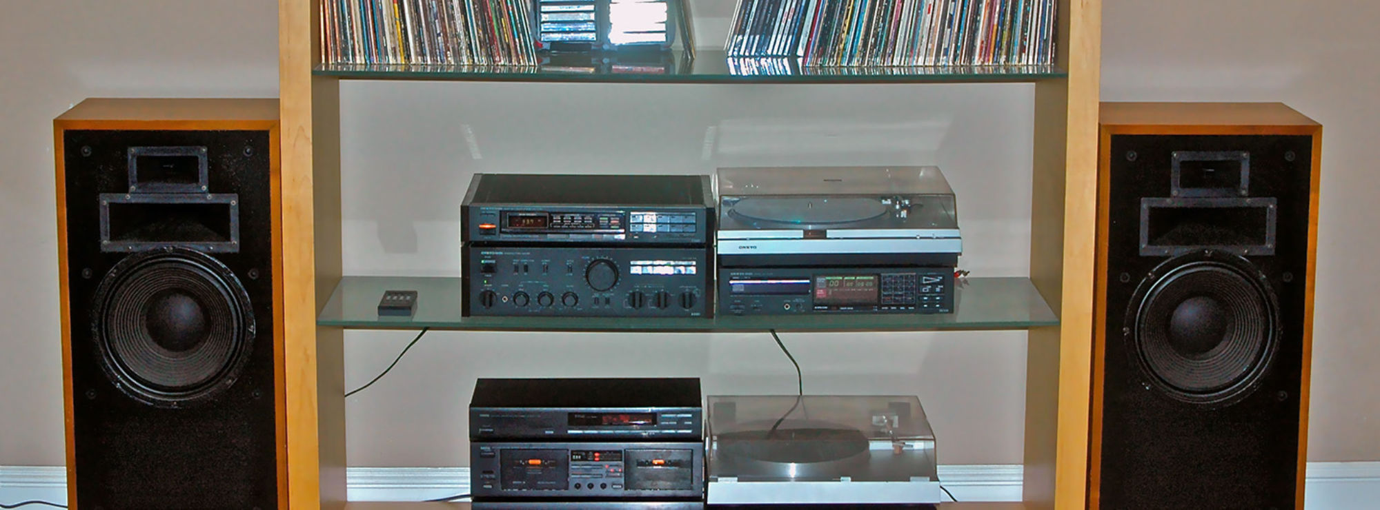 Two Heresy speakers around a shelving unit with records and multiple record players