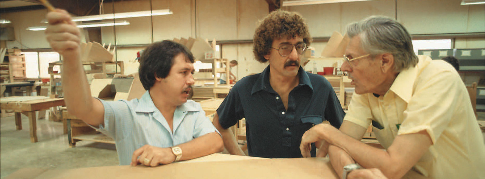 PWK talking with 2 employees in the workshop