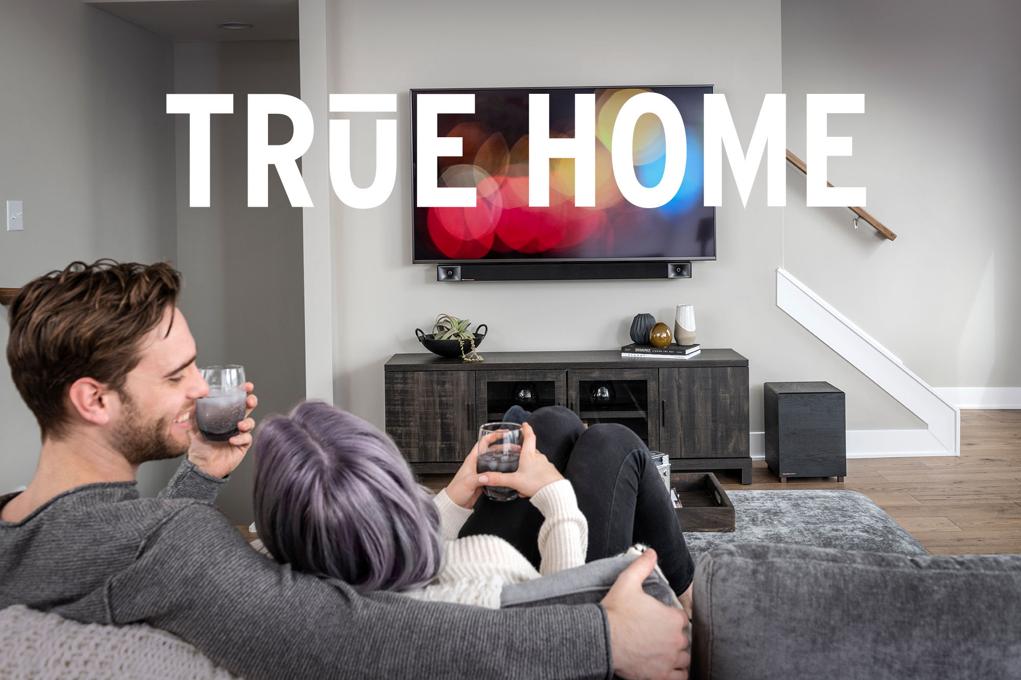 Couple snuggled up on a couch watching TV with Klipsch TRUE sound bar