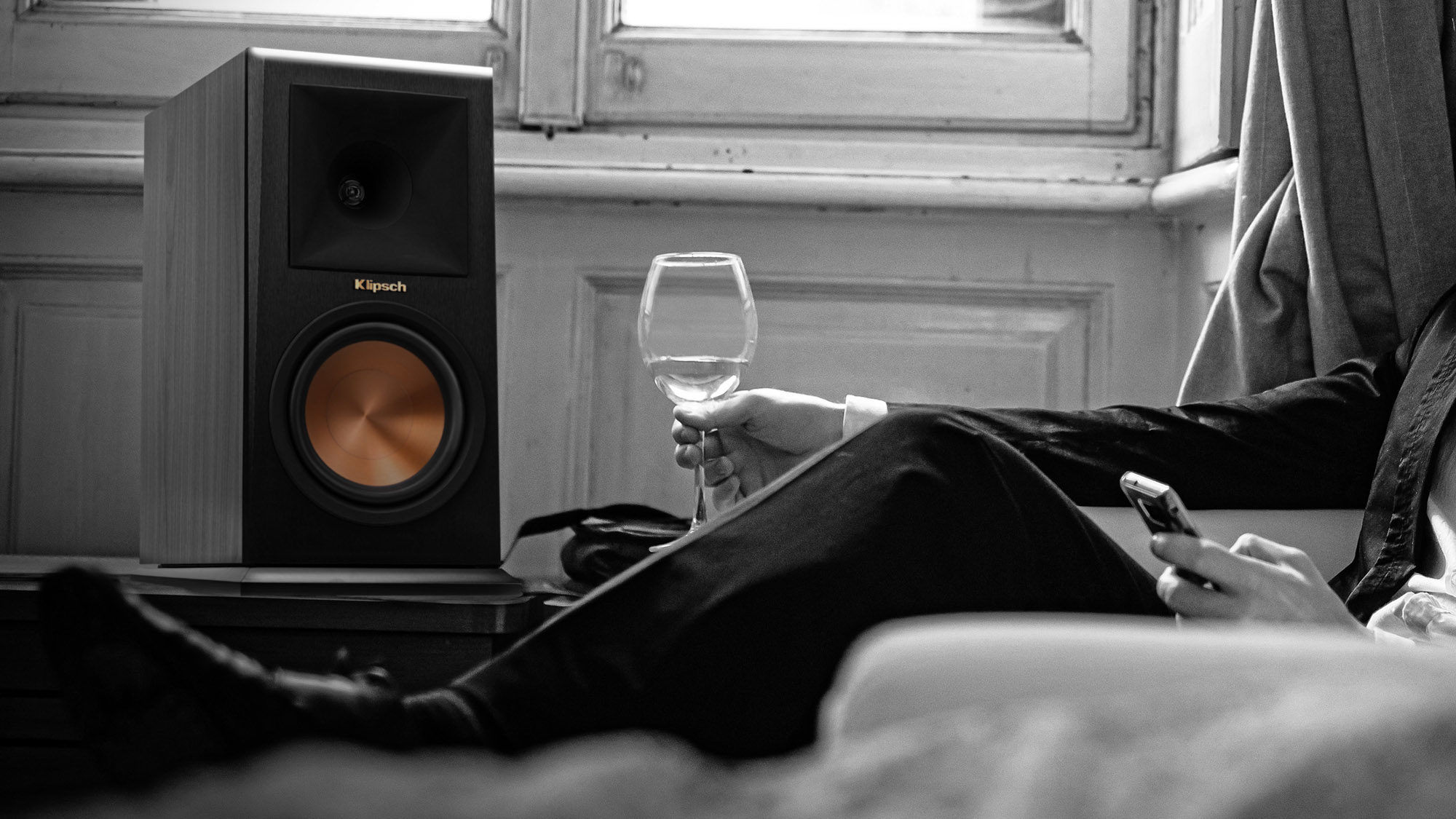 Man drinking wine while listening to Klipsch Bookshelf speakers