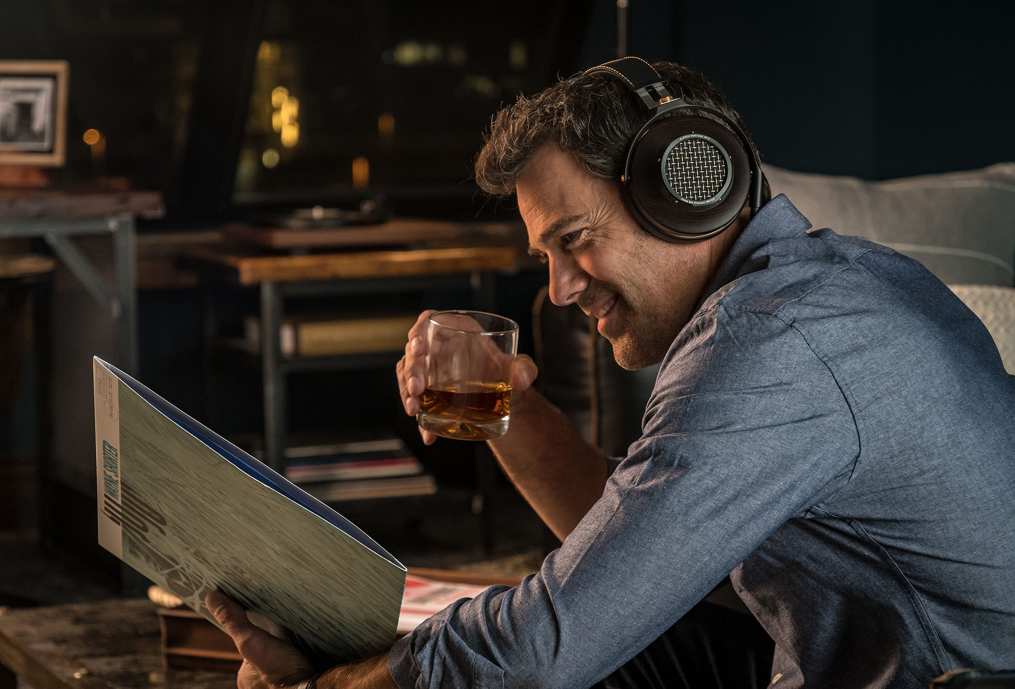 Man drinking scotch and listening to HP-3 Headphones looking at a record