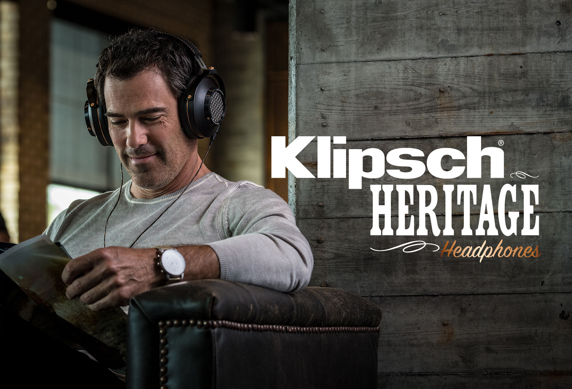 Man reading a magazine on a couch while listening to the Heritage HP-3 headphones