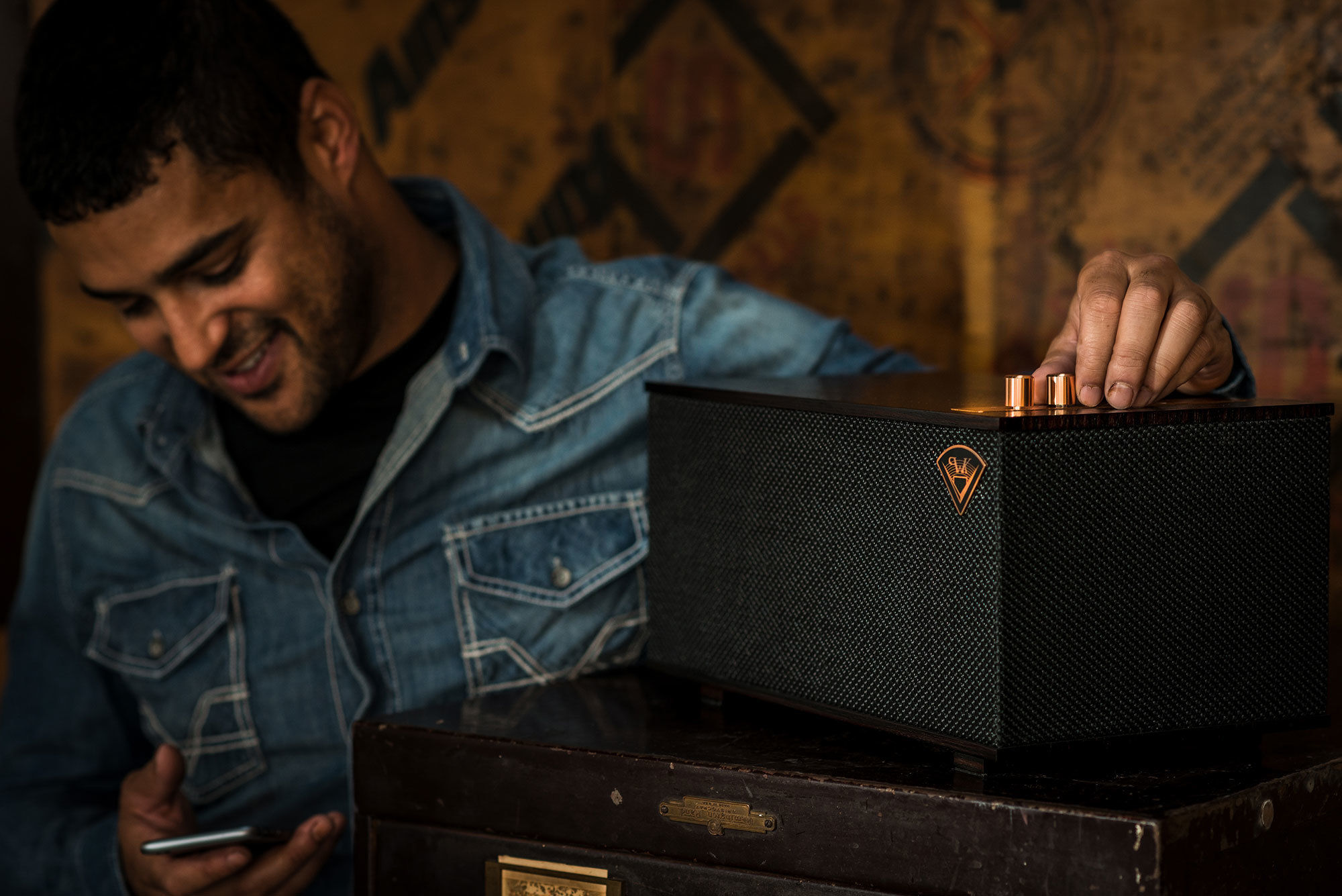 Man checking cell phone and resting hand on Klipsch speaker