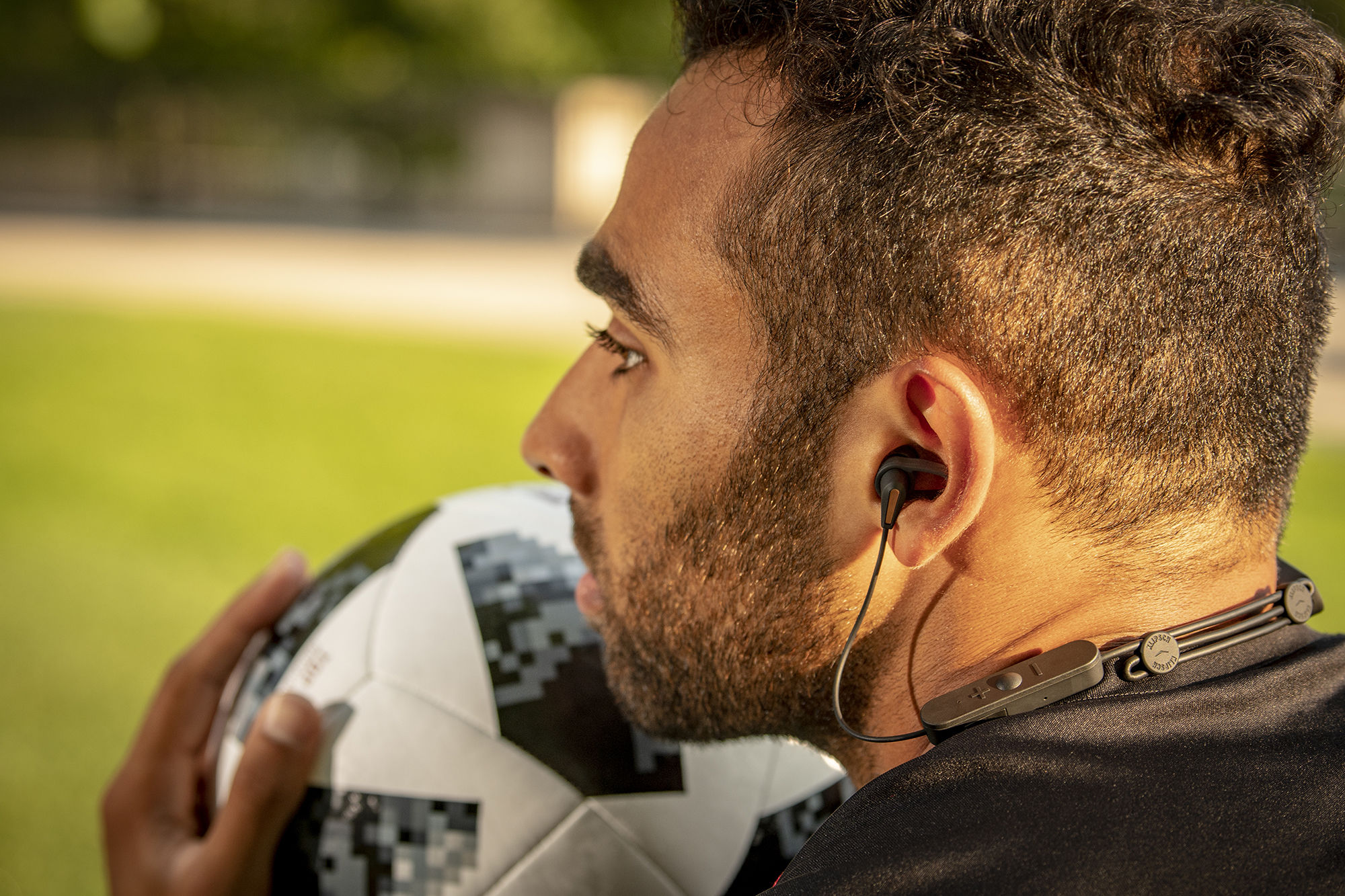 Man holding a soccer ball listening to Klipsch R5 wireless headphones
