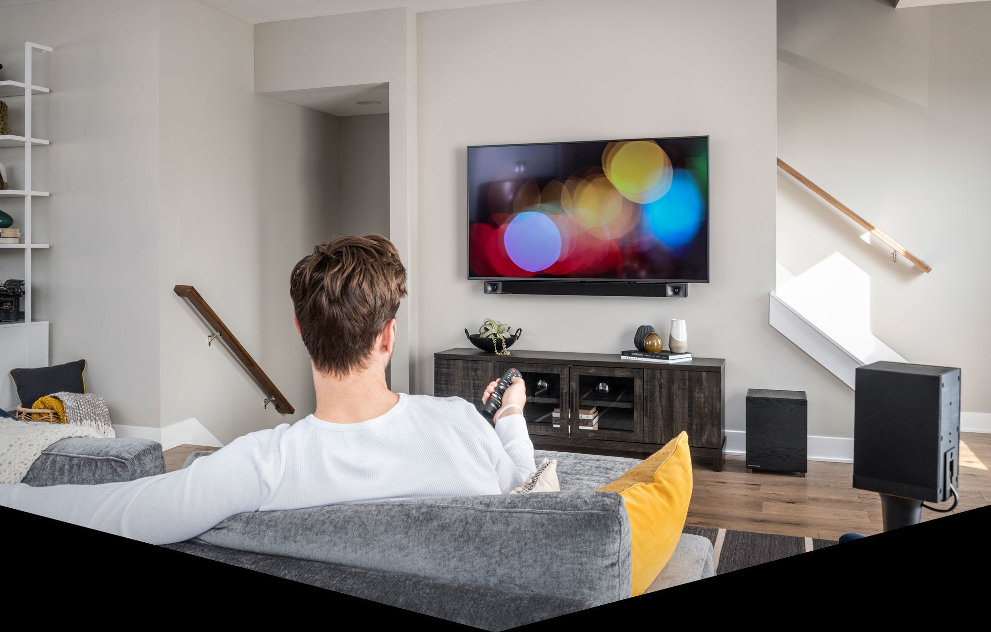 Man watches tv in living room with Bar 48 5.1 Surround Sound System