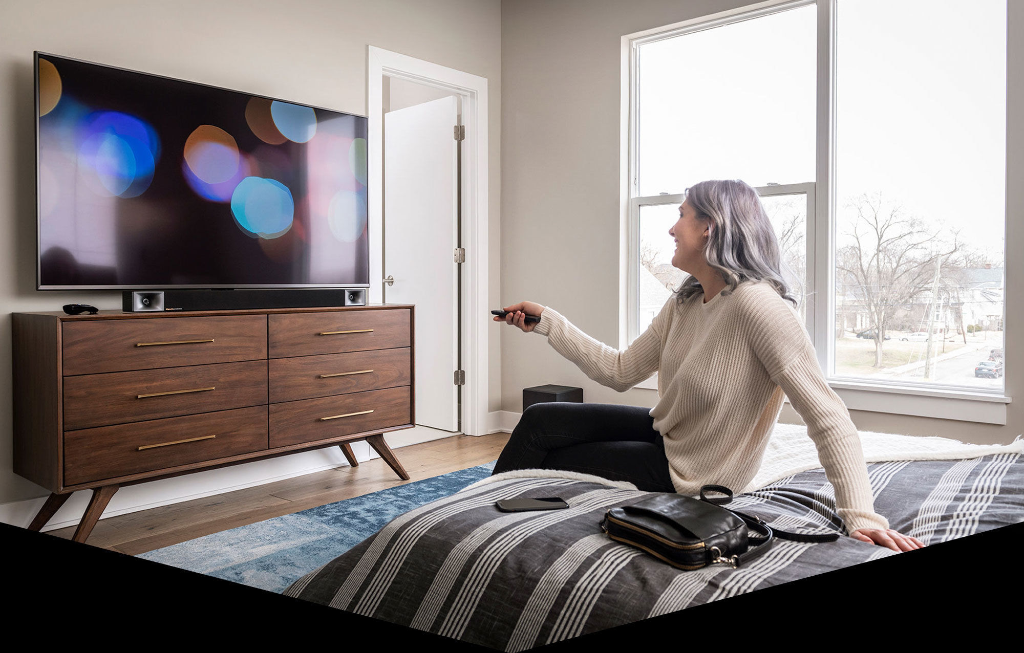 Woman watches tv in bedroom with Klipsch Bar 40