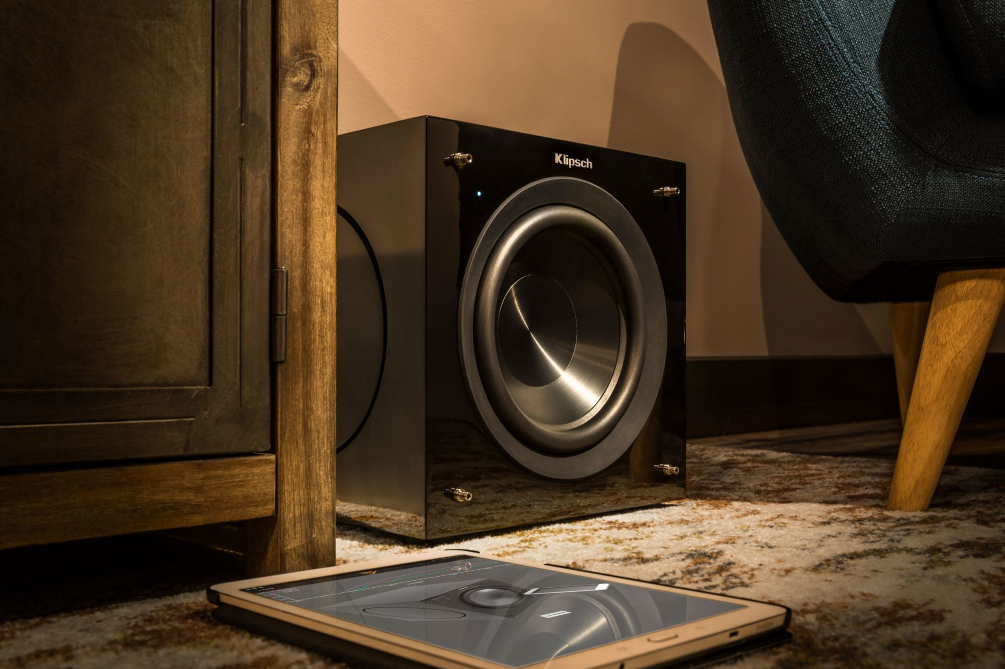 C-308ASWi subwoofer on the floor next to a tablet
