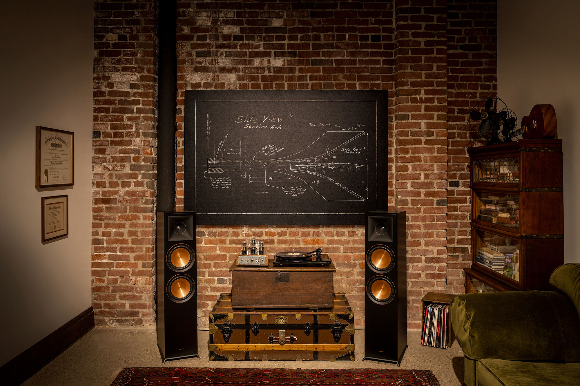 Klipsch speakers near a couch and blueprint on a wall