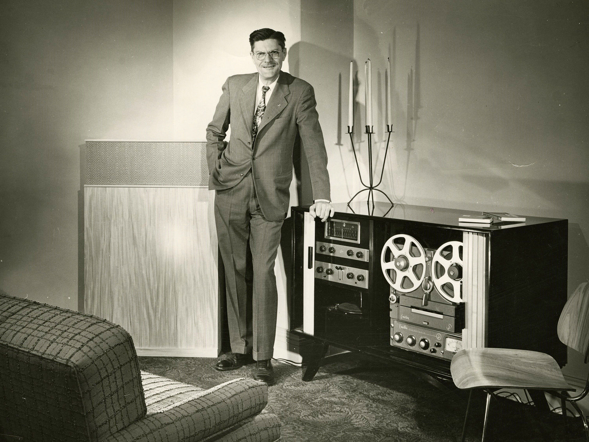 Man stands next to old speaker system (black and white)