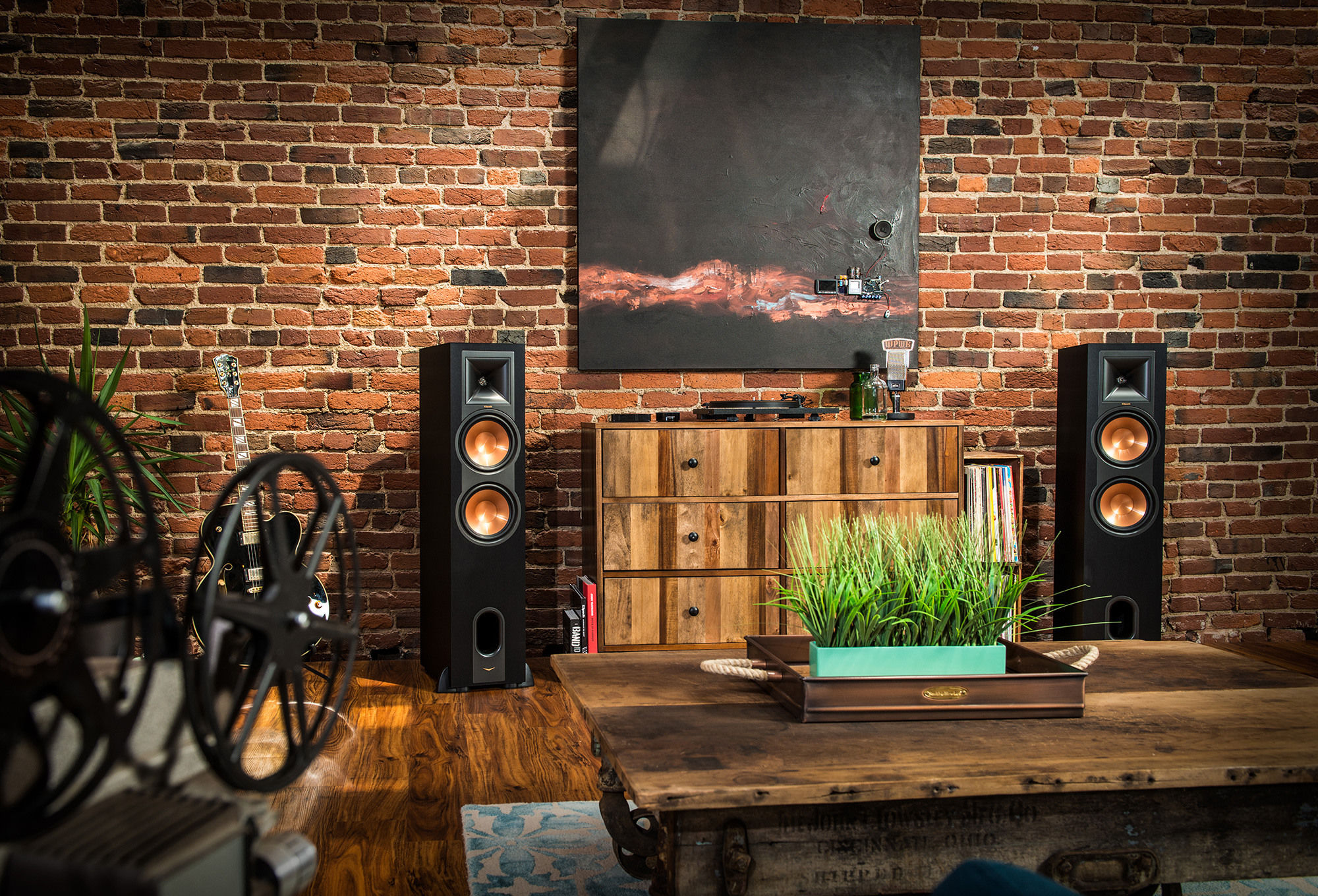 Two R-28PF powered floorstanding speakers flanking a painting and dresser