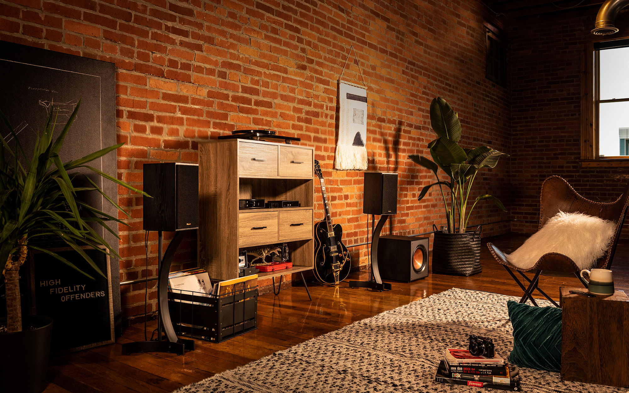 Klipsch speakers with a guitar and wooden shelf