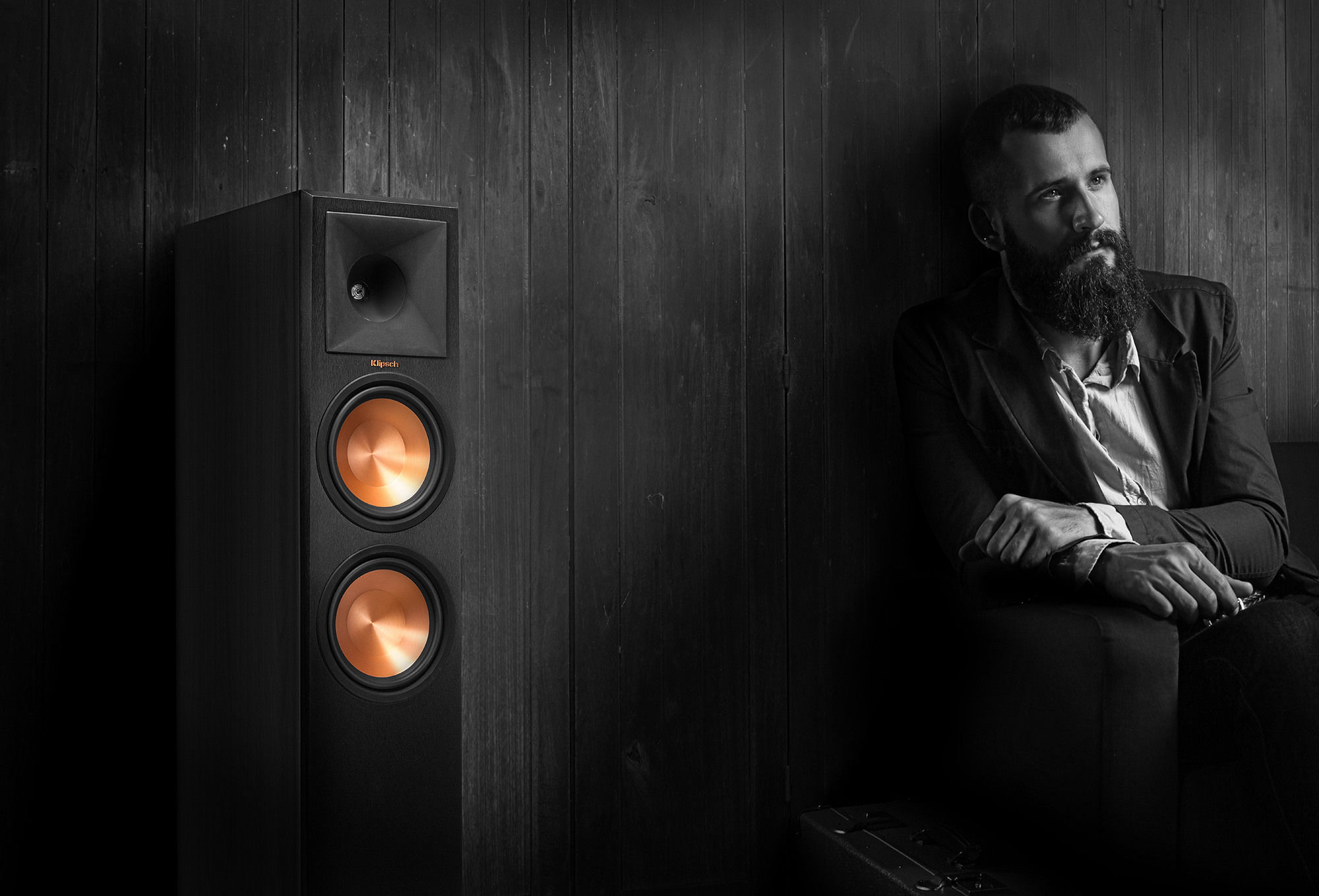Man on a couch listening to a Klipsch floorstanding speaker