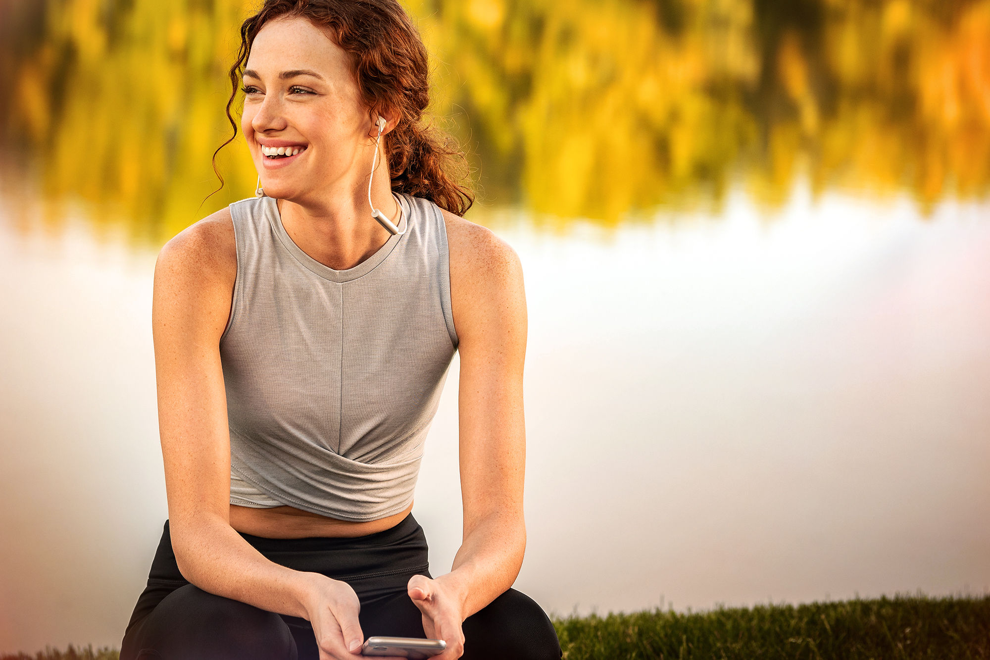 Woman sits by pond with T5 Sport earphones