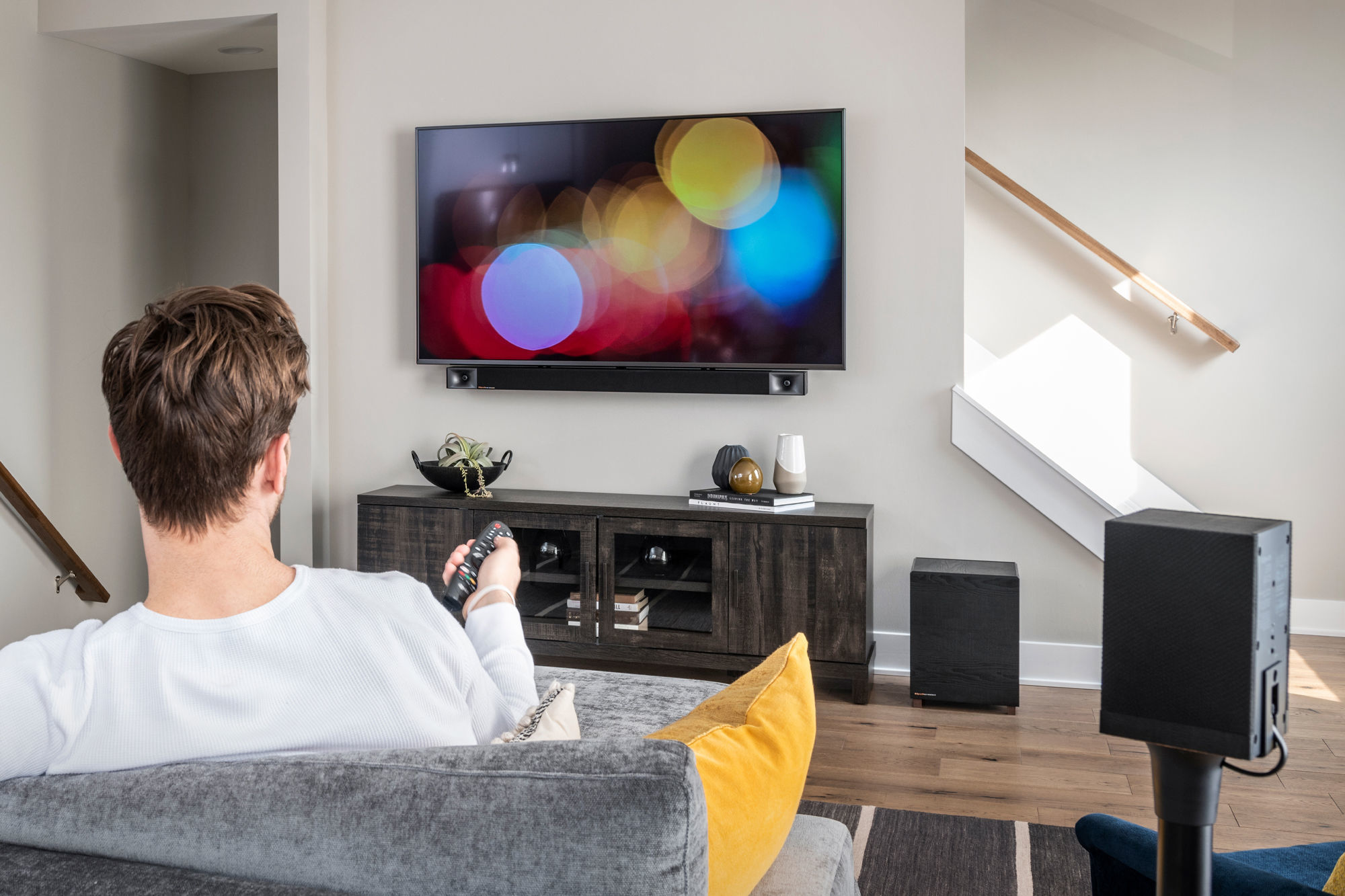 Man watching TV using Klipsch TRUE Sound Bar and Surround 3 speakers