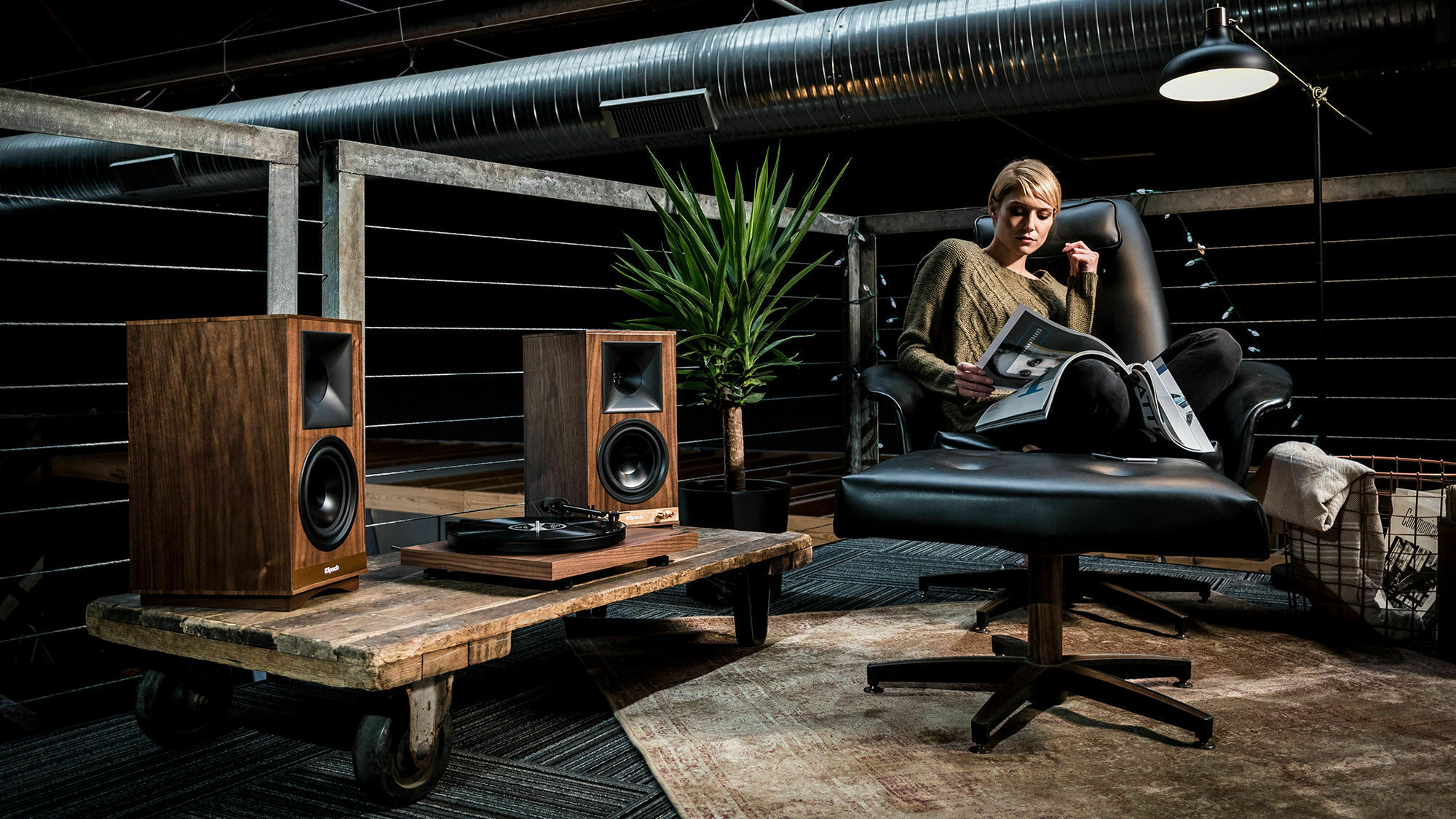 Klipsch The Sixes powered speakers next to turntable with woman listening