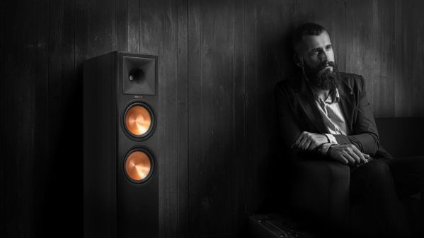Man seated next to a Klipsch Reference Premiere speaker