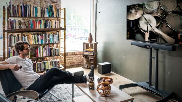 Guy watching tv in living room with RSB-6 sound bar and wireless subwoofer